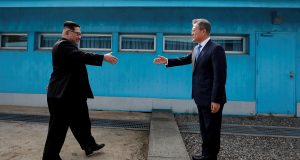 South Korean President Moon Jae-in and North Korean leader Kim Jong Un about to shake hands for the first time at the truce village of Panmunjom